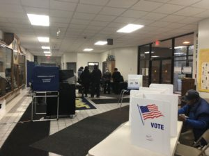Blue and white voting booths are set up in a hallway. Double doors lead to tables of ballots and scanning machines.