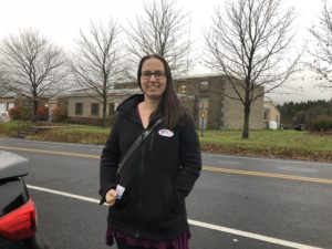 "Smiling woman wearing ""I voted"" sticker and standing outside of brick building."