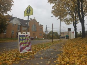 """Vote Here"" sign under children crossing sign with fallen leaves on the ground."