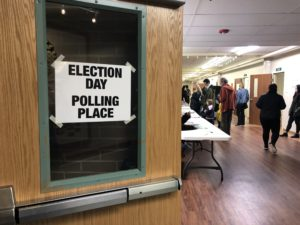 "Sign that says ""Election Day Polling Place"" with people in line in front of a table."