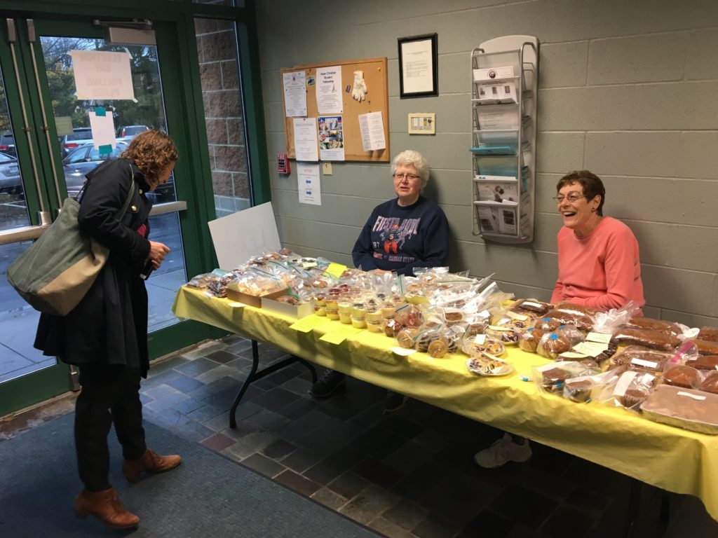 Two women sitting one woman standing next to a table with baked goods