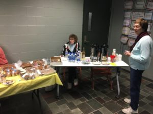 one woman sits and one woman stands next to table with baked goods