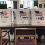 """Three white dividers with an American flag and the word """"vote"""" printed on them sit on a table, where an elderly woman fills out her ballot."""