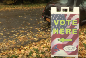 "A sign reads ""Vote Here"" with an arrow pointing toward the polling entrance. There is an American flag background on the sign."