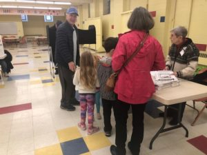 Two grandparents and their granddaughters speak with election inspectors.