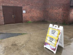 "A sign outside a polling place reading ""Voting Enter Here."""
