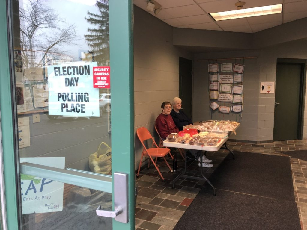 Jackie Sadowski and Evelyn Disinger sit inside the entrace of the Erwin First United Methodist Church polling place.