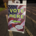 Photo of the Vote Here sign at the polling station.