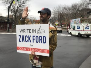 Man holding his campaign sign while waving on Election Day