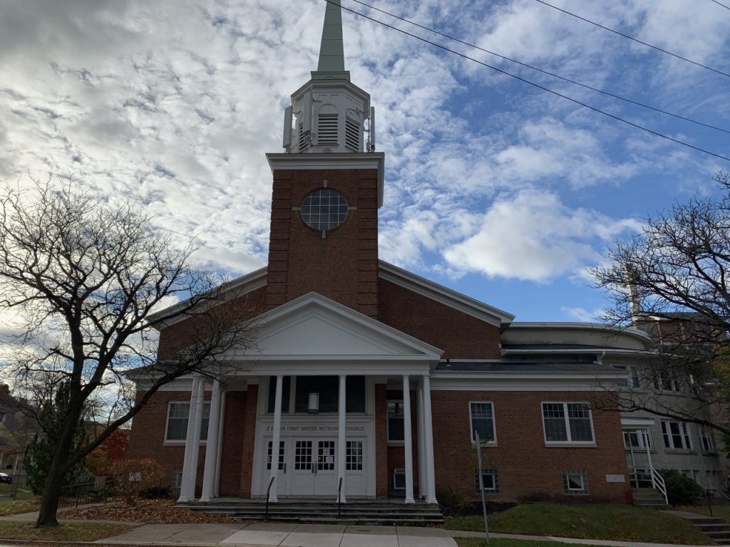 A red brick church building with white pillars and accents.