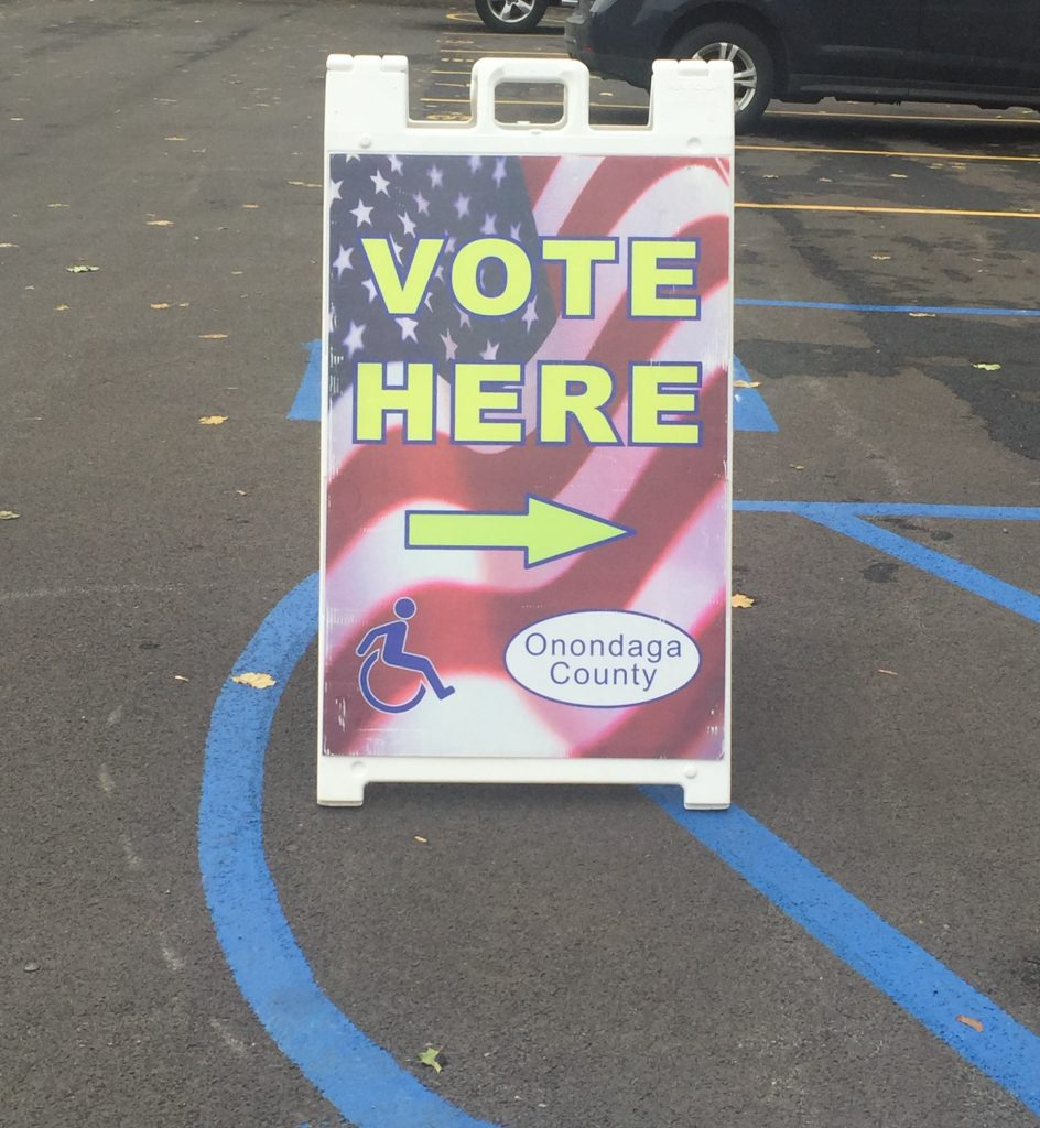 """Sandwich board sign that reads """"Vote Here"""" in yellow lettering over an American flag background."""