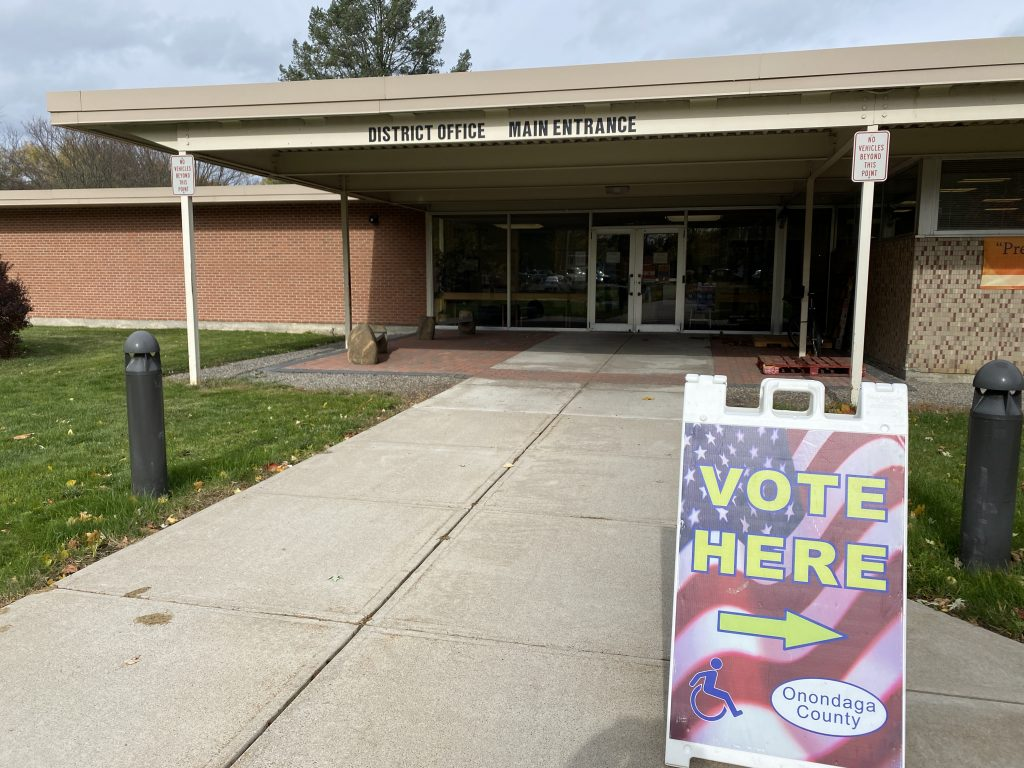 """liverpool school district office with """"vote here"""" sing in front of it"""