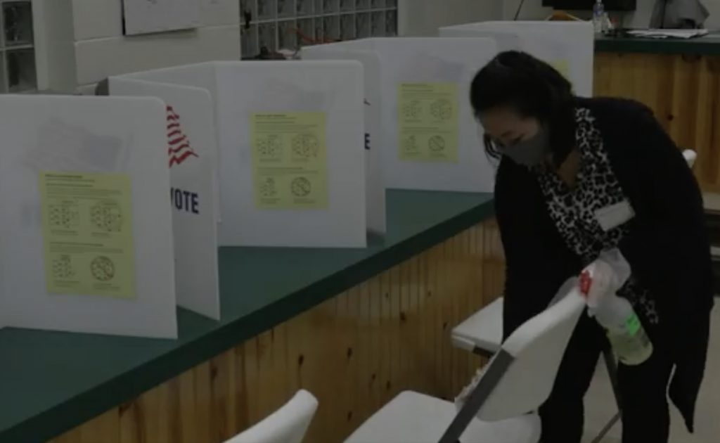 A poll worker wipes down the seat of a voting booth