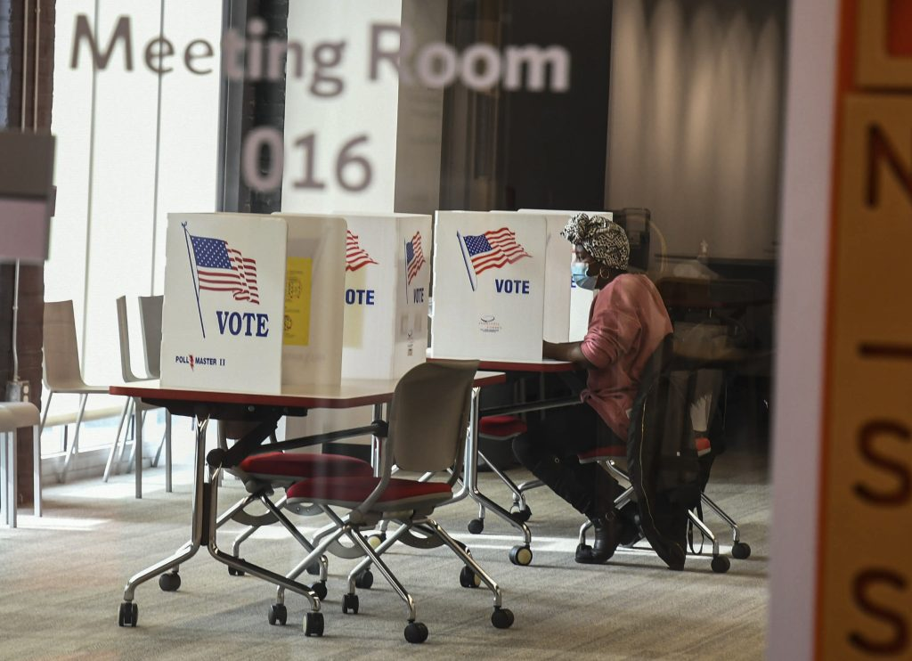 A woman casts her ballot at the polling center in SU's Nancy Cantor Warehouse. (Photo by Hannah Graf)