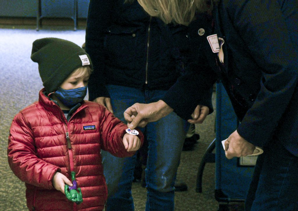 A volunteer at the Skaneateles Fire Station hands out a sticker to a child who voted with his mother on Election Day. Photo by Gillian Follett.